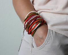 I call this color combo The Triumphant Return of Fall Colors: Off White, Blood Orange, Olive Green, Cranberry --- This listing includes four skinny t-shirt strands all made from real recycled t-shirts and given new life as fabulous accessories for you! They can be worn as bracelets, necklaces or even as a belt. When I first started creating this style I was just looking for ways to use the parts of the t shirt that I couldnt create continuous strands from. However, they quickly became my…