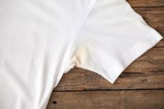 Deodorant stains are easy to pick up, but they're also easy to remove! Learn six ways for removing deodorant stains from clothes with this simple guide. Vinegar Uses, Vinegar And Water, White Vinegar, House Cleaning Tips, Cleaning Hacks, Remove Deodorant Stains, Life Cheats, Laundry Hacks, Wooden Background