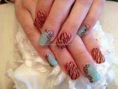 Orange and aqua polish with animal print freehand nail art over acrylic nails