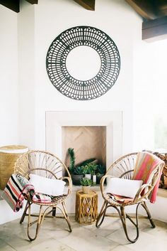 Living space with two circle woven chairs, and a circular mirror above the fireplace