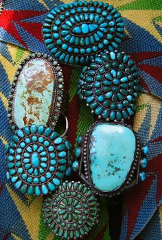 """Posted as """"turquoise rings"""" Or are these large turquoise pieces bracelets? There is a small ring peeking out from under one of the big ones."""
