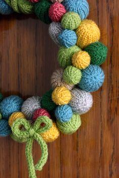 oh, wie putzig! Gestrickte Bommelchen - mit viel pastellfarbener Frühlings-Wolle - ganz fein aufgereiht und zu diesem einzigartigen Türkranz verarbeitet. Kuschelig einladend ziert er am Strickband z.B. eine Tür oder eine Wand.
