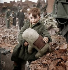 Abandoned boy holding a stuffed toy animal amid ruins following German aerial bombing of London, 1940 color