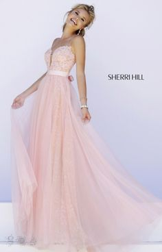 Blushing in lace and tulle, this gorgeous Sherri Hill 32229 gown let's you show off your girly, romantic side. The gown features a plunging V neckline with a fitted lace bodice and dainty tiny crystals. The whimsical lace skirt of this dress has a tulle layer for extra detail. Our favorite part, the adorable satin tie that can be worn in the front or the back. This dress is ideal for a prom, formal gala, or pageant.