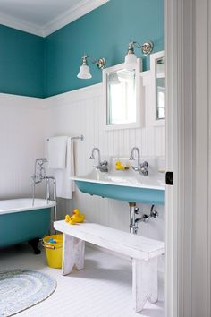 Bold teal paint livens up this cottagey children's bathroom, where it covers a vintage clawfoot tub, old-fashioned sink and walls above crisp white paneling.