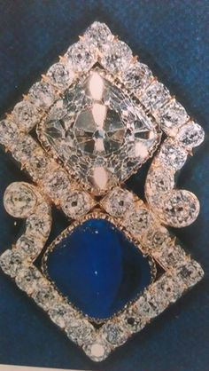 The brooch is the Queen Mary Russian brooch featuring a large square cut diamond and sugarloaf-cut sapphire set into scroll frame.