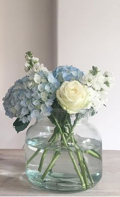 Hydrangeas in pale blue and a perfect cream rose in water and glass. Two summer favourites and a perfect combination floral arrangement