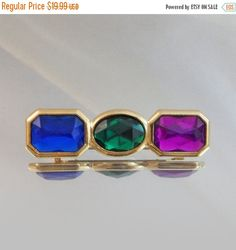 This #vintage rhinestone brooch is a sparkling beauty!  It features a gold tone setting of three stones in royal blue, emerald green and magenta purple. Rolling C-clasp clos... #ecochic #etsy #jewelry #jewellery #holiday2014etfs
