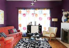 As paredes em tons de berinjela e ameixa absorvem toda a atenção. A cortina colorida é o ponto alto da sala de estar com lareira, recheada de peças antigas e contemporâneas. O resultado é divertido e retrô