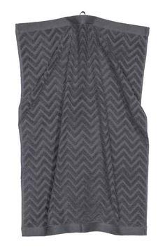 Drap de bain: Drap de bain en coton éponge avec motif zigzag en tissage jacquard. Patte de suspension sur les largeurs.