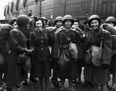 Some members of the ATS were on the dock to greet the first contingent of American WAACs when they arrived in Britain. First Lt.Jean Geherin, Auburn,New York, Shakes hands with Pte.Anne Roberts, Butterglen,Glasgow,Scotland while T/4 Violet Bachman, Long Island,New York and 1st Lt.Helen I.Glenn, Macon,Ga. take their first look round ~