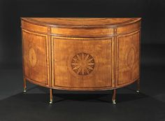 1815 A George III Satinwood, Tulipwood, Rosewood, and Marquetry Commode, Attributed To Mayhew and Ince The demi-lune shaped top with molded edge and central sunflower and fan inlay with a rosette and bellflower-inlaid crossbanded border with plain frieze between urn-inlaid blocks and central cupboard door with intricate rosette medalion