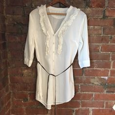 Converse tunic blouse with suede waist tie. Converse tunic blouse with suede waist tie. Ruffles accents around neck and on chest. Covered buttons. Just off white. Perfect condition. Converse Tops Blouses