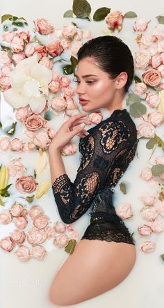Attractive girl in bath with milk and rose petals in lace shirt. Spa treatments for skin rejuvenation.