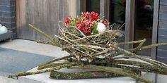Osterdeko: Osternest aus Holunderzweigen und Frühlingsblumen
