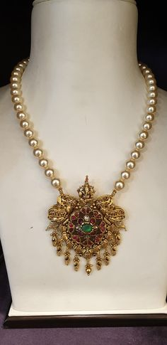 Beautiful pearl chain with gold pendant. Pendant studded with rubies and emeralds. Pendant with swiming swan design. 04 May 2019 Antique Jewellery Designs, Gold Earrings Designs, Gold Jewellery Design, Bead Jewellery, Beaded Jewelry, Necklace Designs, Diamond Jewellery, Wedding Jewelry, Beaded Necklace
