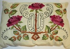 """Vintage Arts & Crafts era embroidered linen pillow from the 1910-1915 period.  The pillow measures about 18"""" x 13"""" and features fuchsia roses with green and brown leaves and ornate needle work."""