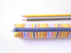 Small pencil case/zipper pouch with distressed stripes in yellow, grey, blue and salmon on a white background, with a grey zip and lining