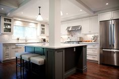 In this split, the ceilings were coffered and recessed lighting was added. A support post remains but helps frame the kitchen. This island must be amazing for entertaining and cooking. Photo courtesy of Sweet Maple.