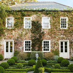 """Rebecca Christina, """"Gorgeous Formal Charleston Garden: The 1743 Home of Ben and Cindy Lenhardt,"""" Traditional Home. The brick is covered in climbing white roses, an espaliered magnolia, and (on the corner) a potato vine (with blossoms less prosaic than its name)."""