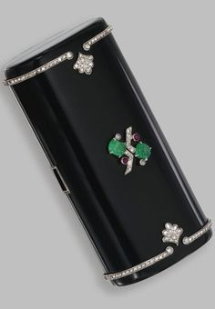 GOLD, PLATINUM, DIAMOND AND COLORED STONE 'NECESSAIRE DU SOIR', CARTIER, FRANCE, CIRCA 1925 The oval form case applied with black enamel, set with carved emeralds, cabochon rubies and rose-cut diamonds, the interior fitted with three covered compartments, a mirror, lipstick and faux tortoiseshell panel, signed Cartier, Made in France, French assay marks.