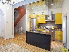 petite cuisine avec îlot central et armoires jaune canari