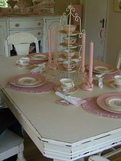 White distressed table. Pink vintage plates. Sparkly placemats, pink teacups and pink candles. It's like heaven. Check out the teacup holder. I'm going to look out for that when I shop. It's a stunning centerpiece. Love the painted dining table too.  Sincerely, JoAnne Craft.