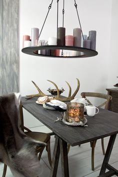 Metall-Lüster für romatisches Kerzenlicht im Wohnzimmer oder Esszimmer. Passend dazu eine gemütliche Tischdekoration mit Hirschgeweih und diversen Tischaccessoires.