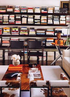 Books & Book Shelves with Orange & browns. Love the cowhide rugs in the modern room.