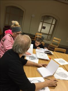 Pendleton Public Library Adult & Teen Coloring Club. The group works on some pictures.