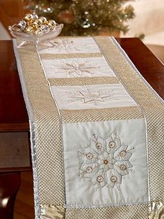 Sparkly Snowflake Table Runner for Christmas  Beautiful metallic snowflakes in five unique patterns waltz down this pretty table runner, perfect for a Christmas table.