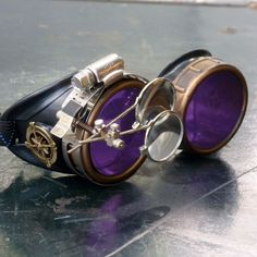 Don this pair of Purple Aviator Steampunk Goggles to standout in subculture crowd. They are blend of technology and aesthetic design inspired by 19th-century industrial steam-powered machinery era. Th