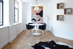 Žaismingas interjeras, subtiliai margos detalės ir minimalistiniai baldai. Prie balto stalo, sienų priderintas pakabinamas šviestuvas OAZĖ.