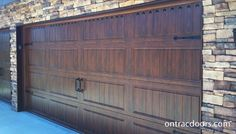 Walnut wood grain finish Clopay Gallery garage door with handles, hinges and clavos.  see more at www.ontracdoors.com
