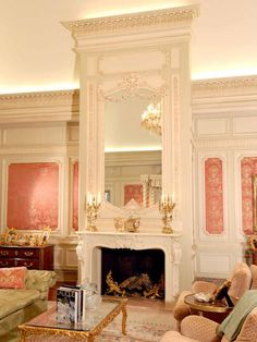 These sitting area walls are a pale sage green with ornate vanilla moldings plus coral and gold fabric panels. The centerpiece is an exact replica of Marie Antoinette's fireplace and mirror. Source: HGTV (no photo credit given.)