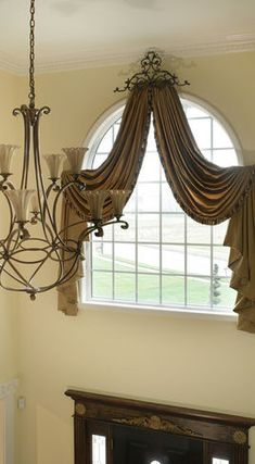 Drapes and curtains for arched windows are designed to create a softer look and highlight the architecture of the foyer. The top valance drapes around the arch. Metal, wrought iron, handmade medallion works with the foyer chandelier creating unity. Curtains For Arched Windows, Window Drapes, Drapes Curtains, Valances, Window Scarf, Scarf Valance, Tall Windows, Curtain Panels, Round Windows