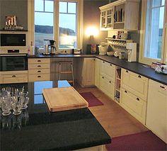 Kulutettu, valkoinen keittiö täyspuisista ja valmiiksi kootuista JUVIn kaapeista.