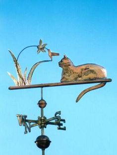Cat with Hummingbird Weathervane by West Coast Weather Vanes. This handcrafted all copper cat weathervane features glass eyes and brass whiskers. Customers can provide photographs of their feline pets for a customized  weather vane depicting  their favorite kitty.