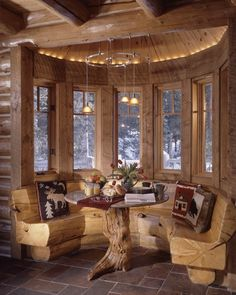 Log cabin breakfast nook. Just love the rounded window design, and how the seats are built in. Great table design.