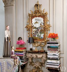 From Iris Apfel's apartment, featured in the June 2011 issue of Architectural Digest.  The stacks of books with colorful binding and the gaudy mirror appeal to me.