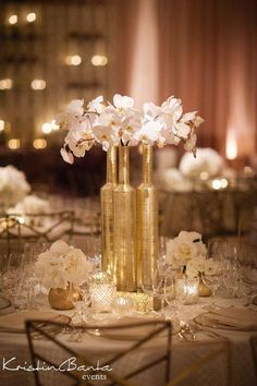 Chic white and gold hues give these circular tables a soft, feminine touch while tall centerpieces add contrasting height. But silver Gold Wedding Centerpieces, Bottle Centerpieces, Reception Decorations, Centrepieces, Centerpiece Ideas, Fake Flower Centerpieces, Black And Gold Centerpieces, 50th Anniversary Centerpieces, White Wedding Decorations