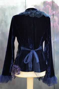 Mysterious dark blue stretchy velvet jacket, altered couture, with delicate sparkling crystals encrusted tulle flounces, laces and intricate details. Hems are adorned with various vintage textiles, laces and appliques, accentuated with hand beading with blue beads, small ab crystals, hand sculpted lush purple silk blooms with Collar features layers of soft tulle, vintage trims, handmade florals, the sleeve ends are trimmed with soft dark blue tulle. Fastens with lace ribbons. Waist can be…