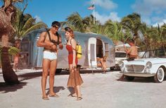An idyllic, hypercolor scene of an Airstream Clipper RV on a tropical spearfishing vacation (ca. 1960). NOTE: What's the make, model and year of the car to the right?