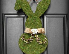 ~Faux Boxwood and Burlap Bunny Wreath with Geranium Tail ~ A complete Etsy original. Thank you so much for visiting my shop! Im so thrilled you found this one of a kind design here! This custom designed wreath will make you so HOPPY this Easter!  It begins with an exclusive wooden bunny design that is woodworked in my studio and wrapped in burlap for the base. The darling is layered with lush, faux boxwood and the bunny is accented with a beautiful rustic burlap bowtie to match its burlap…
