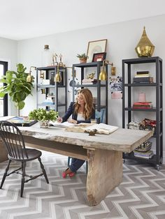 When she's not filming, Genevieve works out of this converted bedroom. At nearly 10 feet long, her desk—which is actually a raw mahogany dining table by Timothy Oulton—offers plenty of room to spread out. Behind her, metal CB2 shelves hold books, fabric swatches, and her Telly awards. Genevieve laid the floor tiles in a chevron pattern that mimics the herringbone hardwood in the other rooms.
