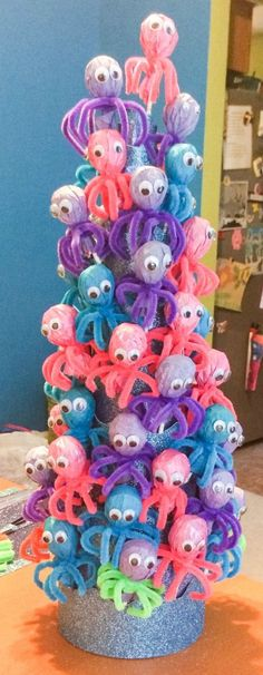 Use a foam cone and Tootsie roll Pops for this Octopus Tower Bach Centerpiece - Life's a Beach, Enjoy the Waves with these Beach Inspired Party Ideas on Frugal Coupon Living.