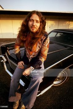 Photo of David COVERDALE and DEEP PURPLE; David Coverdale, posed, sitting on bonnet of car