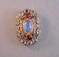 Hobe sterling gilt dress clip with a central blue cabochon
