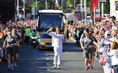 Olympic rowing gold medalist James Cracknell carries the Olympic Flame through Kingston Upon Thames, London
