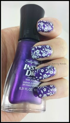 white flowers on purple nail art